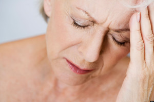 A senior woman with a headache, touching her forehead